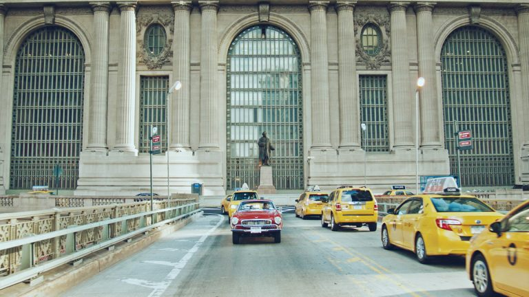 Shot of Irv Gordon driving his 3 million mile car in front of Grand Central Station, New York.