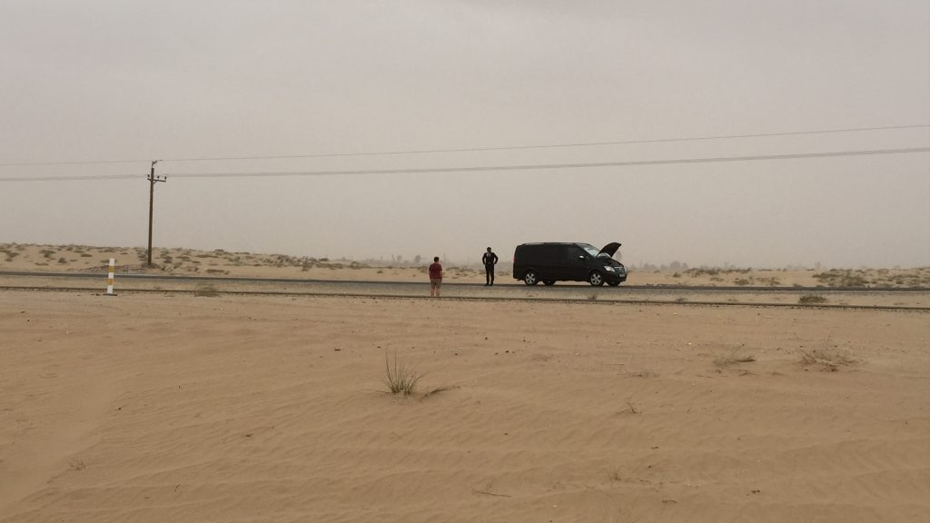 An image of a production vehicle broken down in the desert.