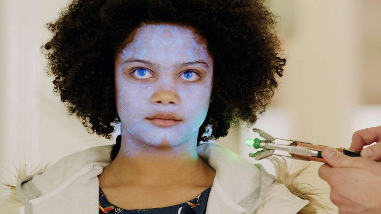 Doctor Who visual effects shot of a device casting a blue pattern on a young girls face