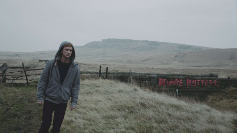 'In the flesh' visual effects shot of a man walking through a field. On the dry stone wall behind him is graffiti saying 'Beware Rotters!
