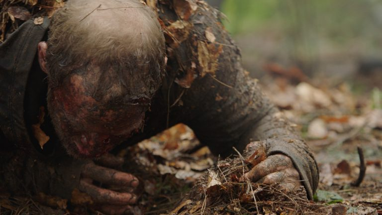 'Paranoid' visual effects shot of a man covered in dirt and leaves, crawling through a woodland floor, seemingly injured