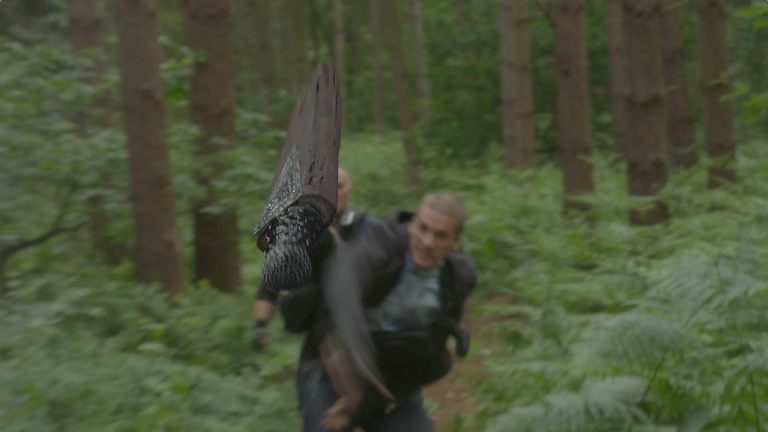Young Dracula visual effects shot of a man in a forest throwing a stake-like prop