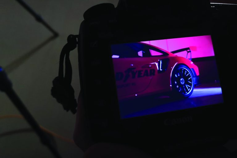 Shot of a red Porsche in a studio, through a monitor